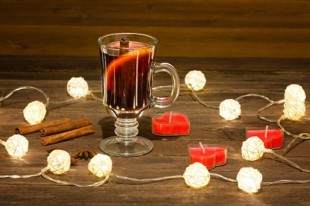 Tazza di vin brulè con spezie, candele a forma di cuore su un tavolo di legno
