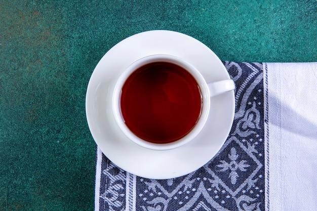 Tazza di vista superiore di tè sull'asciugamano di cucina su verde