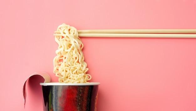 Tazza e bacchette di noodles istantanei su uno sfondo rosa.