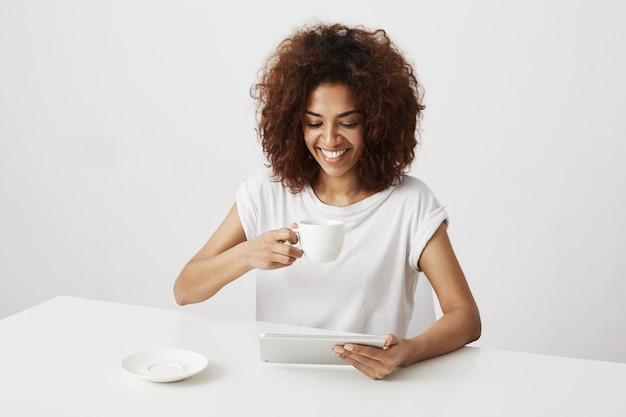 Tazza e compressa della tenuta sorridenti della ragazza africana che si siedono alla tavola sopra la parete bianca.