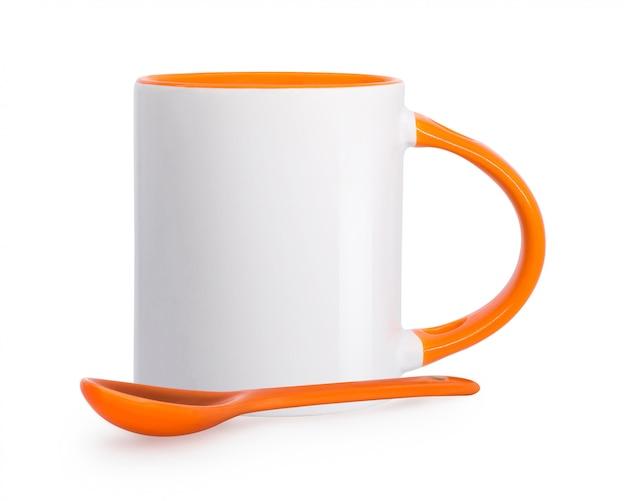 Tazza e cucchiaio di ceramica isolati su fondo bianco.