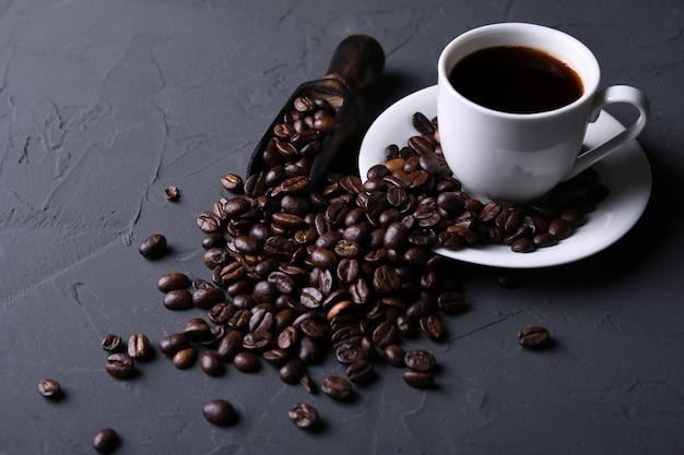 Tazza e fagioli di caffè sul vecchio beton grigio della cucina, tavola della roccia. con copyspace per il tuo testo