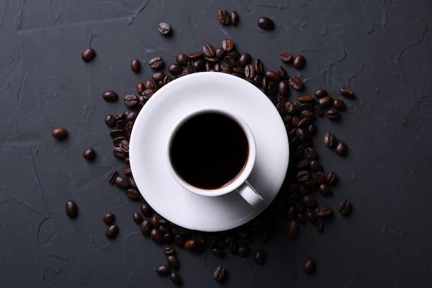 Tazza e fagioli di caffè sul vecchio beton grigio della cucina, tavola della roccia. vista dall'alto con copyspace per il testo