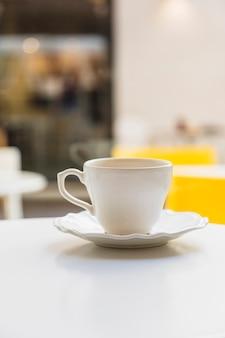 Tazza e piattino di ceramica sulla tavola bianca contro il fondo della sfuocatura