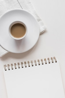 Tazza e piattino di tè sopra il tovagliolo con il blocco note a spirale contro fondo bianco