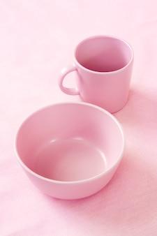 Tazza e piatto rosa sul fondo rosa delicato del panno