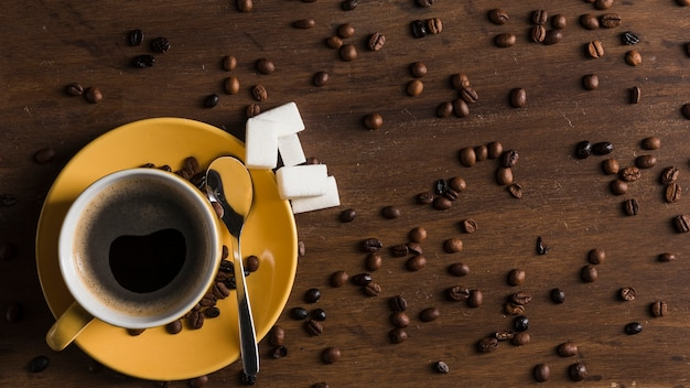 Tazza gialla con blocchi di zucchero e piatto vicino a chicchi di caffè