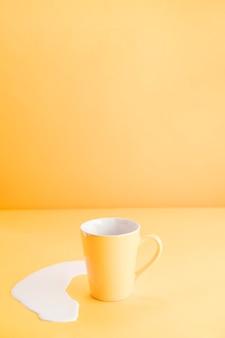 Tazza gialla con latte versato
