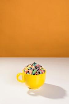 Tazza gialla dell'angolo alto con i cereali sulla tavola