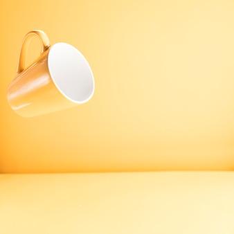 Tazza gialla galleggiante con copyspace