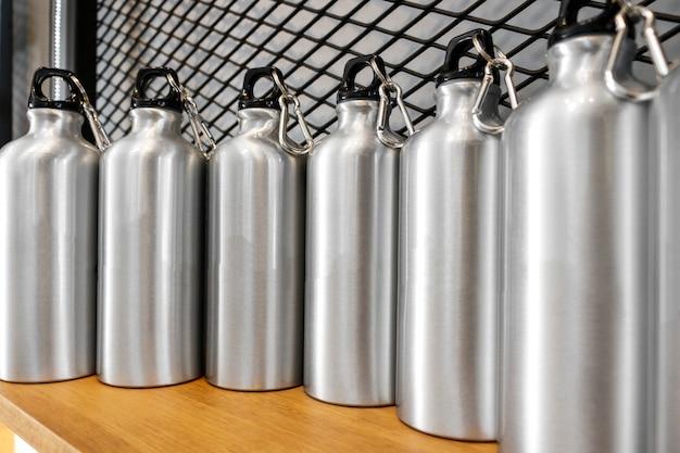 Tazza in acciaio su mensola bianca. bicchiere inox vuoto