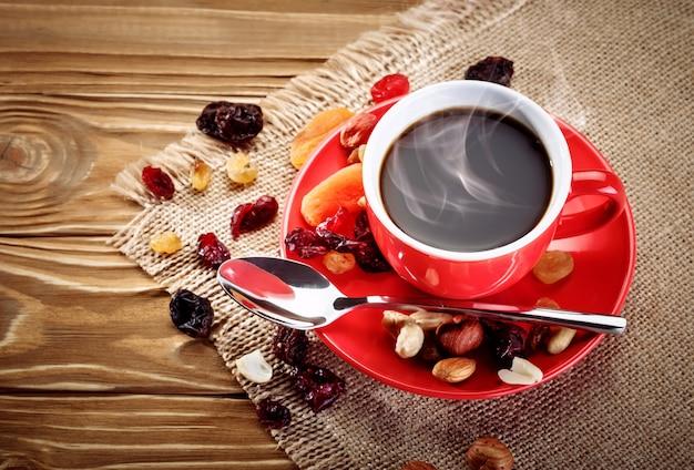 Tazza in ceramica rossa con caffè caldo su tavole di legno.
