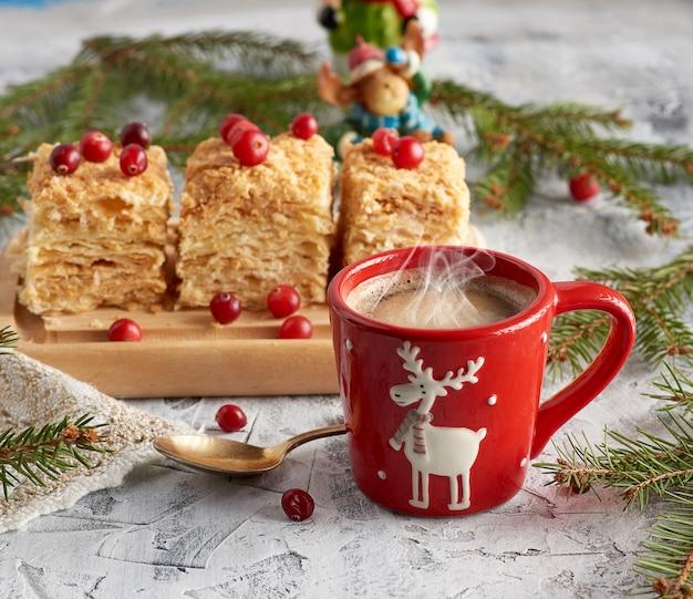 Tazza in ceramica rossa con caffè nero e fette di sfogliatina napoleone con crema al burro