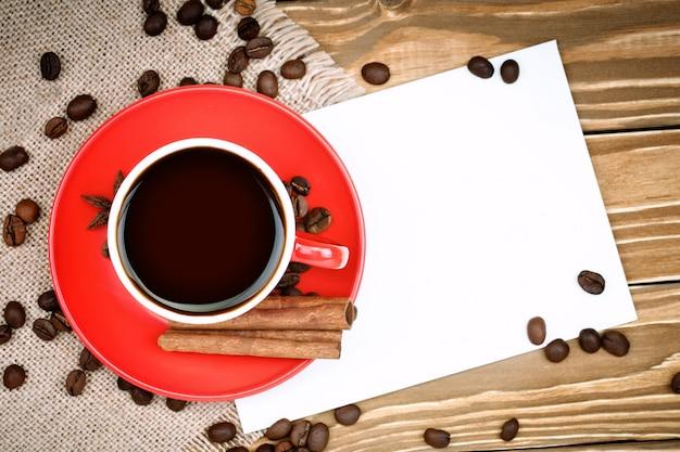 Tazza in ceramica rossa con supporto di caffè su tavole di legno e tela da imballaggio con chicchi di caffè sparsi.