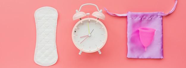 Tazza mestruale con borsa, cuscinetto igienico, sveglia su sfondo rosa.