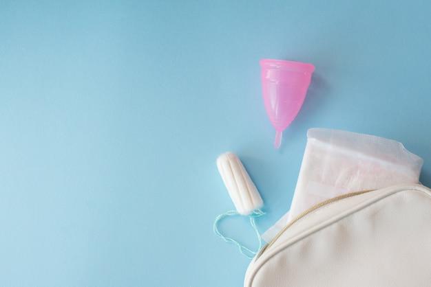 Tazza mestruale, cuscinetti e tampone con borsa bianca su sfondo blu