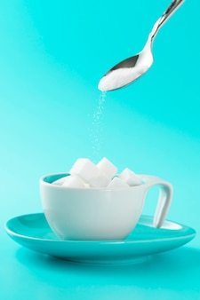 Tazza minimalista con zollette di zucchero e cucchiaio