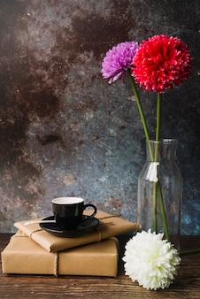 Tazza nera e piattino su scatole regalo di carta marrone avvolto con bellissimi fiori