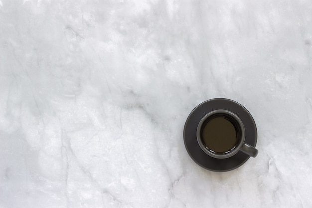 Tazza nera sul piattino con caffè nero sul fondo della tavola di marmo.