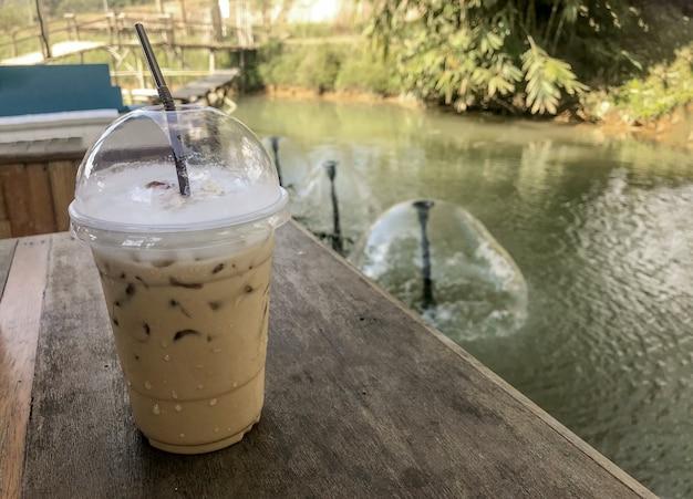 Tazza palstic del caffè di ghiaccio sulla tavola di legno in giardino vicino al fiume naturale.