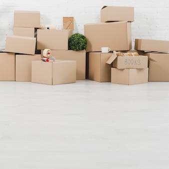 Tazza; pianta; nastro adesivo e libri sulle scatole di cartone nella nuova casa