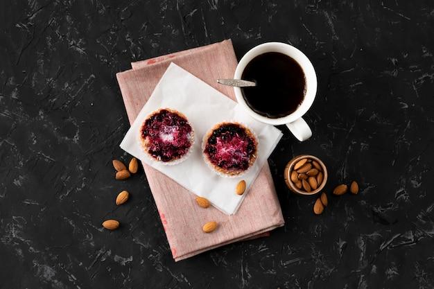 Tazza piatta con caffè caldo, torta dolce su un tavolo nero, colazioni fatte in casa