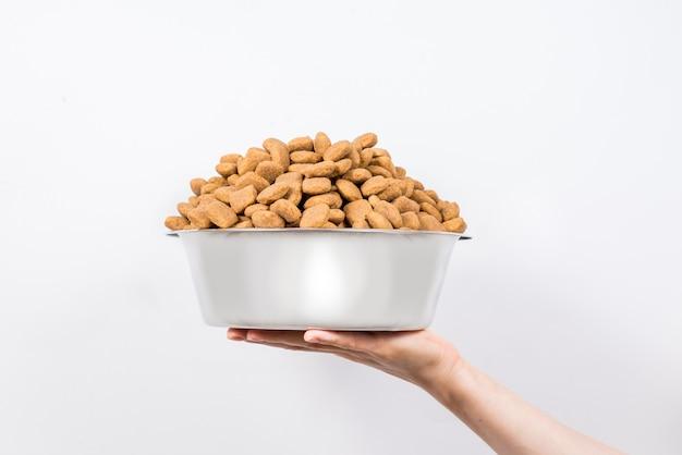 Tazza piena con uno scorrevole di alimento per animali domestici asciutto isolato su fondo bianco