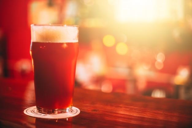 Tazza piena di birra rossa sul bancone
