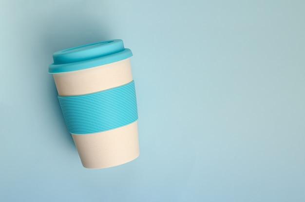 Tazza riutilizzabile in bambù resistente con supporto in silicone su sfondo blu pastello