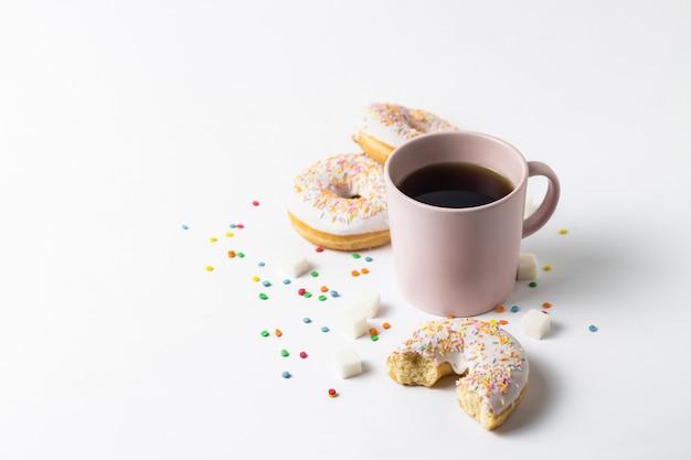 Tazza rosa con caffè o tè e ciambelle saporite fresche, caramella decorativa multicolore dolce su un fondo bianco. concetto di panetteria, pasticceria fresca, deliziosa colazione, fast food.