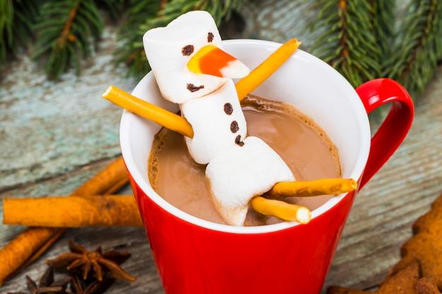 Tazza rossa con cioccolata calda con pupazzo di neve fuso marshmallow