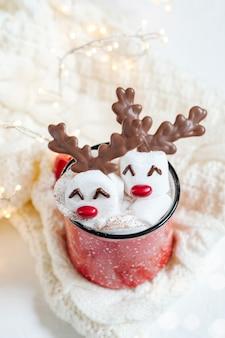 Tazza rossa con cioccolata calda e renna marshmallow sciolta