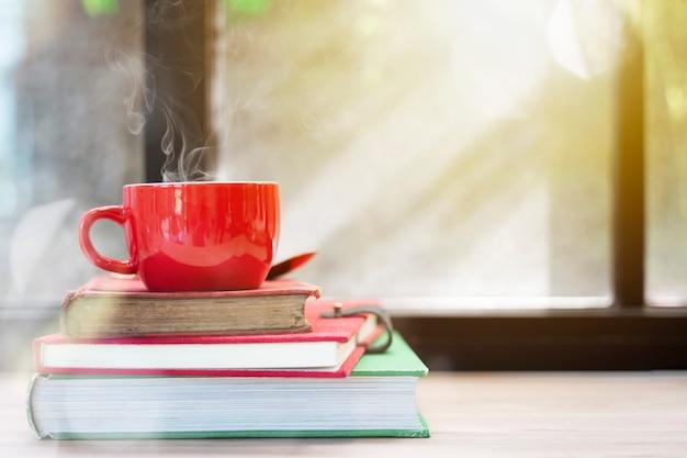 Tazza rossa con fumo in cima ai vecchi libri impilati sulla tavola di legno con la luce della finestra. merry chri