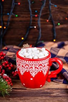Tazza rossa con l'ornamento di inverno con le caramelle gommosa e molle del cacao in decorazioni di natale