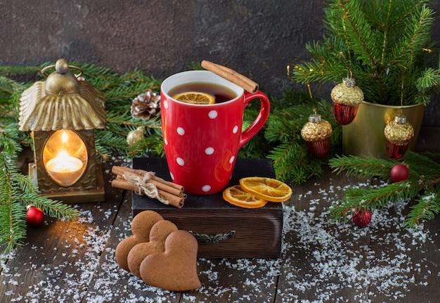 Tazza rossa con tè, una lanterna con una candela, biscotti a forma di cuore, rami di abete e coni