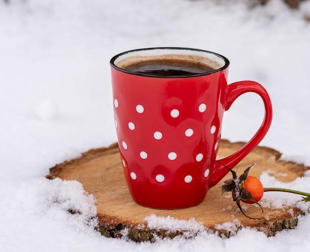Tazza rossa in un punto bianco con caffè nero caldo