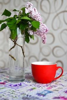 Tazza rossa vicino a un vaso con una pianta