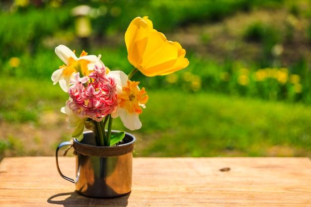 Tazza rustica su una tavola di legno con i fiori, giardino di estate, concetto di rilassamento. fiori della primavera in tazza sul giardino di estate. paesaggio rurale alla luce del sole. stagione estiva.
