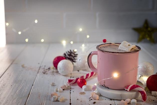 Tazza smaltata di cioccolata calda con marshmallow e bastoncini di zucchero con belle luci natalizie