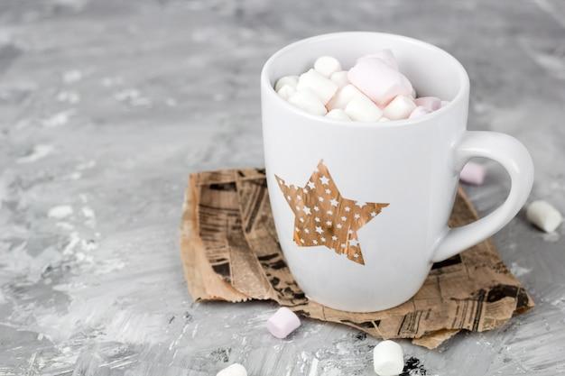 Tazza sveglia con marshmallow su uno sfondo di cemento grigio grunge