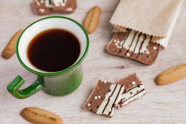 Tazza verde di americano e barretta di cioccolato al latte