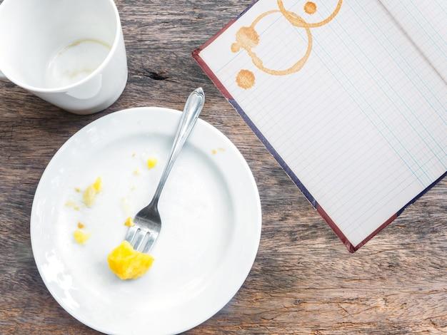 Tazza vuota di caffè, piatto e libro contabile