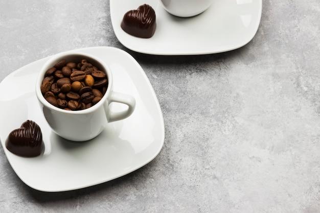 Tazze bianche per espresso riempito con chicchi di caffè e cioccolato a forma di cuore su uno sfondo chiaro. copia spazio