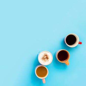 Tazze con bevande calde, caffè, cappuccino, caffè con latte su una superficie blu. concept coffee shop, incontro con gli amici, colazione con gli amici, squadra amichevole. piazza. vista piana, vista dall'alto