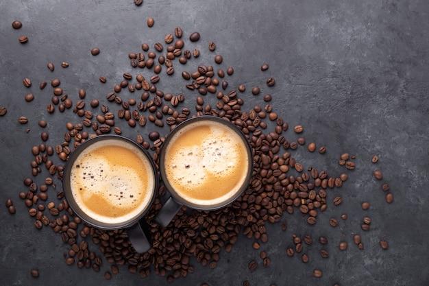Tazze con caffè e chicchi di caffè su pietra scura.