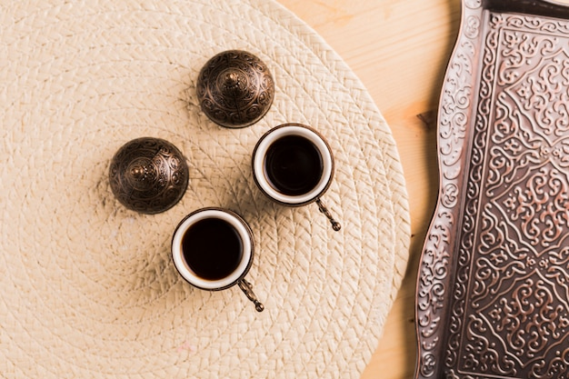 Tazze con caffè nero e vassoio di metallo