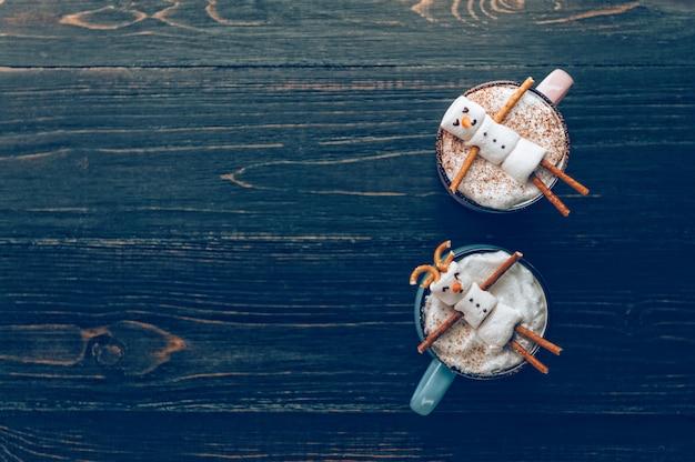Tazze con cioccolata calda in cui gli uomini del marshmallow si rilassano. concetto di coppia