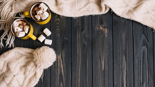 Tazze con marshmallow vicino a vestiti caldi