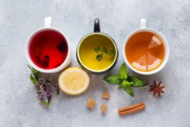 Tazze con tè diverso rosso, verde e nero sul tavolo grigio. menta e limone, zucchero di canna, cannella e anice