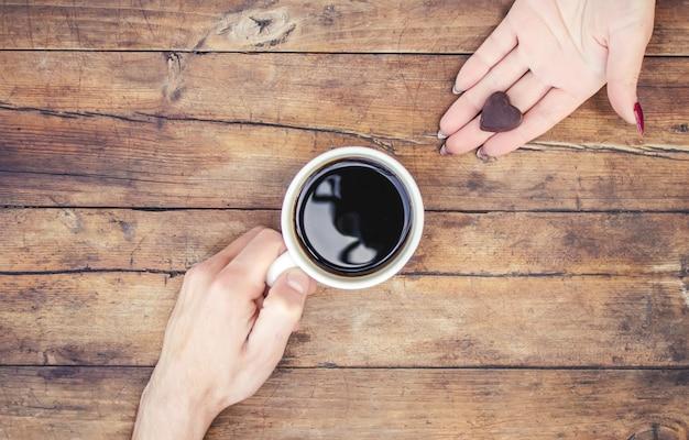 Tazze con un caffè nelle mani di uomini e donne. messa a fuoco selettiva